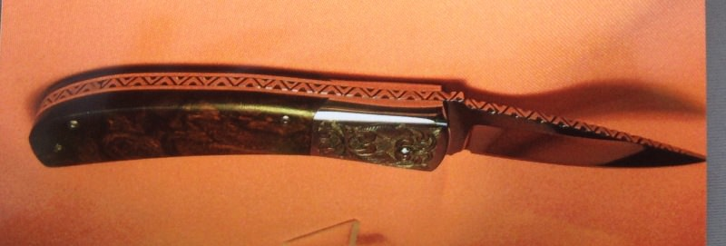 """Another scale release auto with 3 1/2"""" blade of 440-C that is mirror polished. It has burl ironwood scales and is fileworked with engraved bolsters."""